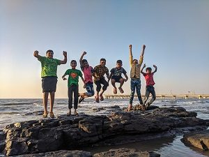 Boys jumping on rock at beach, photo by Ajay Bhargav