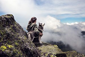 Girl sitting with husky and clouds